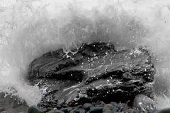 碰撞在一个多岩石的海滩的波浪 库存图片