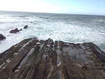 碰撞在一个被腐蚀的岩石的波浪 免版税库存图片