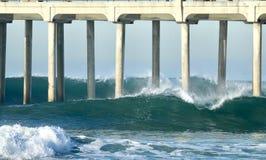 碰撞在亨廷顿海滩码头下的大波浪在橘郡加利福尼亚 库存图片