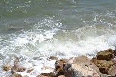 碰撞在含沙和多岩石的海滩的波浪 图库摄影
