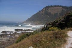 碰撞在多岩石的海滩的山和波浪 库存照片