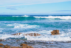 碰撞在岩石、完善的蓝色和水色海洋的波浪浇灌,岩石在岸,在天空的高层云 免版税库存图片