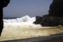 碰撞在岩石和在天空中的强有力的波浪飞溅水在遥远的黑熔岩沙滩在和平的海岸线 免版税图库摄影