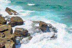 碰撞在岩石平台的波浪 图库摄影