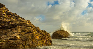 碰撞在岩石的波浪在日出 库存图片