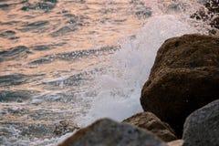 碰撞在岩石的波浪在日落 免版税图库摄影
