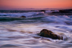 碰撞在岩石的波浪在日落 免版税库存图片