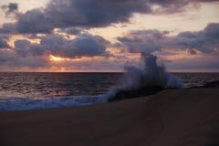 碰撞在岩石的波浪特写镜头,反对美好的日落 免版税库存图片