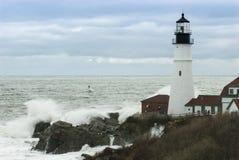 碰撞在岩石的波浪由缅因灯塔当风暴通行证 免版税图库摄影