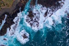 碰撞在岩石的波浪鸟瞰图  免版税图库摄影