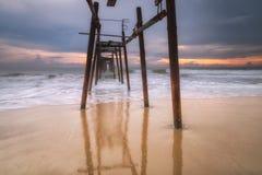碰撞在岸上的日落和波浪 免版税库存照片