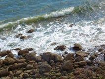 碰撞在峭壁的海 库存图片