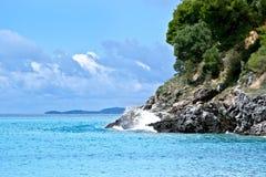 碰撞在希腊的岩层峭壁的波浪 库存图片