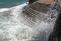碰撞在江边的波浪 免版税库存照片