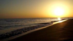 碰撞在沙子海滩海洋的慢镇静令人满意的波浪支持在美妙的温暖的晚上橙色日落海景的海岸线 股票视频