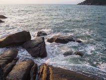 碰撞在沿海石头的波浪在日出 库存图片