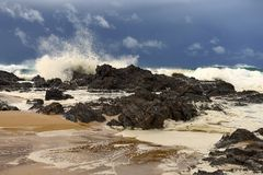 碰撞在海岸线的岩石的巨大的波浪 免版税库存照片