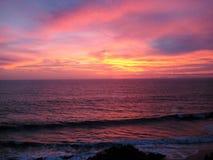 碰撞在海滩的波浪在日落 免版税图库摄影