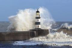 碰撞在灯塔-英国的波浪 库存照片
