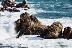 碰撞在点罗伯斯, Carmel,加利福尼亚的岩石的波浪 免版税库存照片