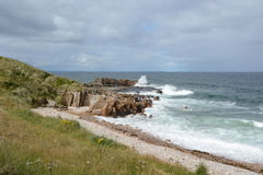 碰撞在砂岩岩石的波浪 免版税图库摄影