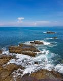 碰撞在蓝天下的黑岩石的波浪在酸值西康省 图库摄影