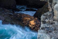 碰撞在金黄岩石的波浪 免版税库存图片