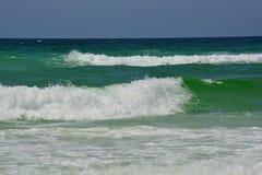 碰撞在鲜绿色海岸的惊人波浪 免版税库存照片