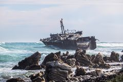 碰撞由一个生锈的老海难的波浪 鸬鹚、海鸥和其他鸟的家 图库摄影
