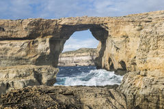 碰撞的波浪和遥远的峭壁在天蓝色的窗口在戈佐岛,马耳他 免版税库存图片