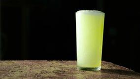 碳酸化合的苏打饮料,黄色在颜色和涌入在黑背景的一块玻璃 影视素材