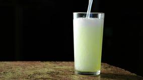 碳酸化合的饮料,黄色在颜色和涌入在黑背景的一块玻璃 股票录像