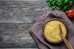 碾碎干小麦、绿色和菜在木桌上 免版税图库摄影