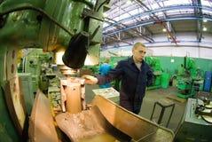 年轻碾碎机器操作员工作在机器 免版税库存图片