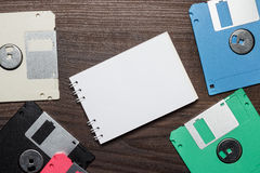 磁盘和空白的笔记本在木背景 库存照片
