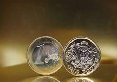 1磅和1枚欧洲硬币在金属背景 库存图片