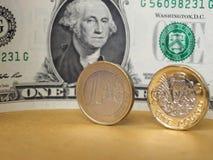 1磅和1枚欧洲硬币和一美元笔记在金属背景 免版税库存照片