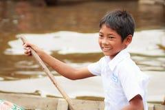 磅士卑Phluk放学回家的划艇的男孩 库存图片