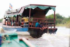 磅士卑PHLUK,柬埔寨- 10月24 :柬埔寨孩子在一个游船背后乘坐到磅士卑Phluk村庄在Octob 免版税库存图片