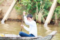 磅士卑PHLUK,柬埔寨- 10月24 :磅士卑Phluk放学回家的划艇的男孩2015年10月21日在磅士卑酸碱度 免版税库存图片