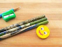 磨削器、铅笔、铅笔笔和橡皮擦在木背景 免版税库存照片