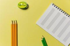 磨削器,笔记本,在一个黄色背景办公室题材的铅笔 免版税库存照片