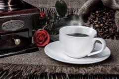 磨咖啡器、红色玫瑰和咖啡在木书桌上的 免版税图库摄影