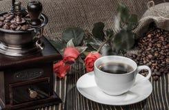 磨咖啡器、红色玫瑰和咖啡在老木书桌上的 库存图片