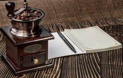 磨咖啡器和笔记本在老木书桌上 库存照片