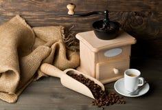 磨咖啡器用咖啡豆和杯子浓咖啡 免版税库存图片