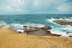 礁石和岩石在海岸阴云密布天气 库存图片