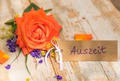 礼品券、证件或者优惠券与德国词、Auszeit、手段暂停和桔黄色玫瑰 免版税库存图片