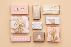 礼品包装材料构成 在金背景隔绝的美丽的北欧圣诞节礼物 桃红色和金子色的被包裹的礼物盒 免版税库存照片