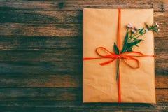 礼品包装材料纸栓与一条红色丝带和一朵雏菊花在木减速火箭的难看的东西背景与空间文本的 免版税库存照片